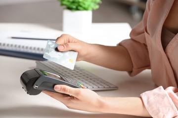 Woman using modern payment terminal at table indoors, closeup