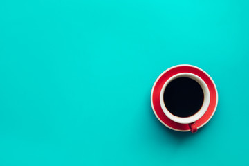 A cup of coffee on colorful pastel background.Top view