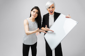 two angry girls holding an empty poster isolated on white background