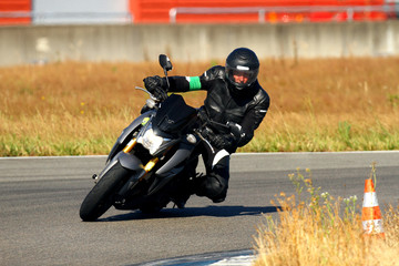 A man leaning over a motorcycle in a curve on a circuit