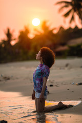Mixed race woman on a tropical beach during amazing sunset.