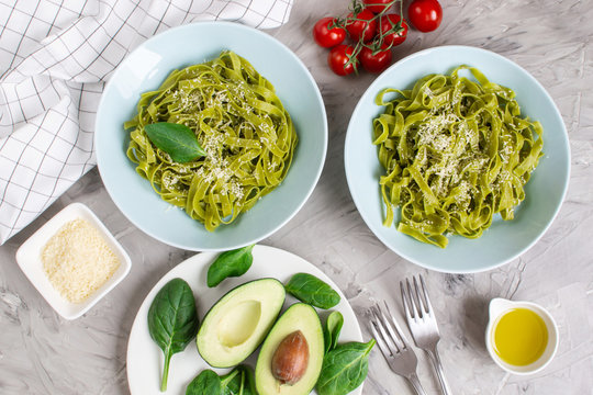 Cooked green spinach tagliatelle pasta on a plate with Parmesan cheese and avocado sauce, Italy food, healthy concept, vegetarian