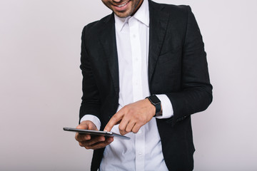 Stylish image of tablet in hands of attractive young man in white shirt, black jacket on white background. Leadership, smart worker, manager, using modern technology, internet, businessman