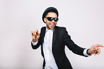 Stylish excited guy in suit, hat, black sunglasses having fun on white background. Leisure, weekends, cheerful mood, joy, happiness, dancer, singing modern businessman isolated