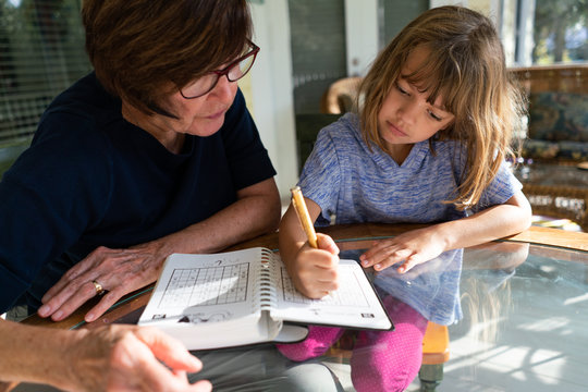 Grandmother and granddaughter doing a math puzzle