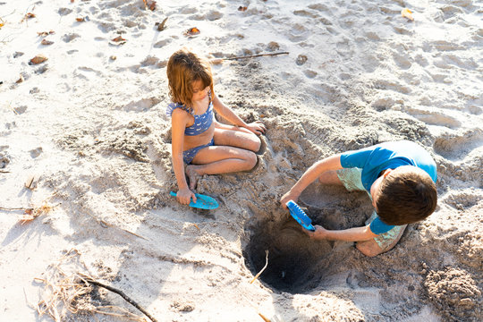 Girl and boy digging a hole in the sand
