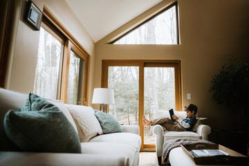 Side view of boy reading book while reclining on armchair in living room at home