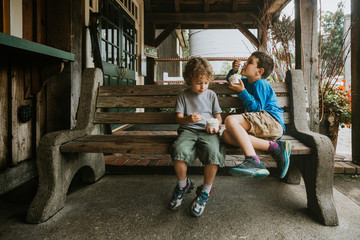 Siblings eating ice cream while sitting on bench