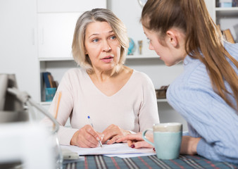 Woman and adult daughter fill out paperwork