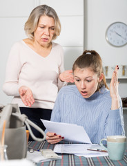 Sad young female and mother with financial documents