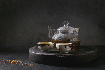 Hot green tea in two traditional chinese clay ceramic cup and glass teapot standing in tray on black marble table.