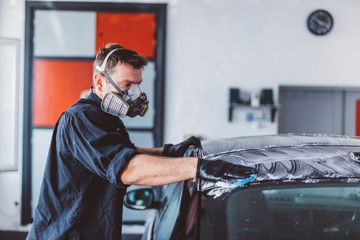 Male worker cleaning car top with soap in workshop