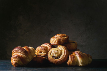 Variety of homemade puff pastry buns cinnamon rolls and croissant on wooden table. Dark still life. Copy space