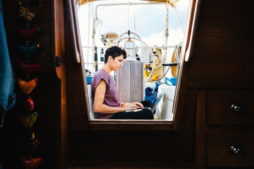 Side view of woman using laptop computer while sitting in boat seen through window