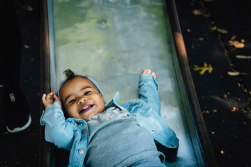 High angle portrait of happy cute baby girl sliding at playground
