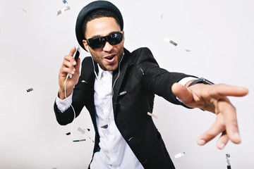 Photo sur Plexiglas Magasin de musique Portrait expressing brightful positive emotions of handsome guy in hat, suit, black sunglasses having fun in tinsels on white background. Celebrating great party, listening to music, leisure, weekends