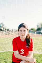Portrait of confident girl wearing red soccer uniform against goal post during sunny day