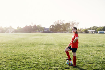 Side view portrait of confident girl with soccer ball standing on playing field against sky during sunny day