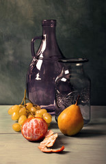 Still life with blue glass vase, lilac glass jar and fruit on turquoise background