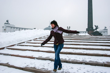 A young woman on the stairs in the winter park. Happy woman jumping on the snow.