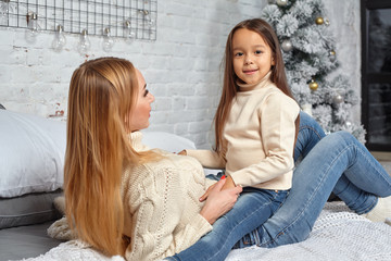 Mother and her daughter child girl playing and hugging on bed