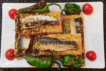 Lisbon, Portugal traditional sardines served food. Close up top view of grilled sardines on toasted bread with olive oil green peppers and tomatoes garnish.