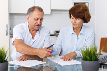 Mature family couple sitting at kitchen table and  signing documents