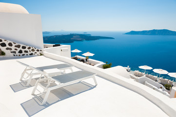 Two chaise lounges on the terrace with sea view. Santorini island, Greece