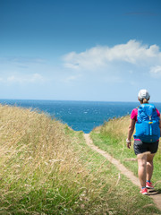 girl with backpack travels along sea coast along Camino de Santiago