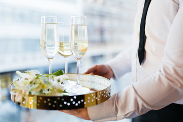 Waiter serving tray with champagne glasses