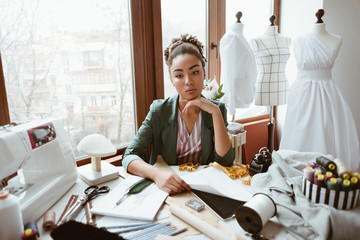 Wall Mural - Fabulous young tailor in design studio. Young woman near sewing machine