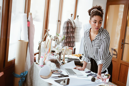 Young fashion designer at workplace, african woman looking to someone.