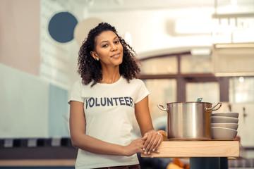 Joyful afro American woman standing near the saucepan