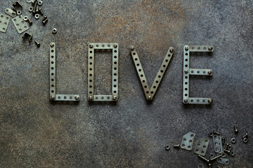 Valentines day abstract background. The word love on a dark background. Valentines day concept. Valentines day greeting card. Wedding concept. Metal letters. Vintage background. Top view.