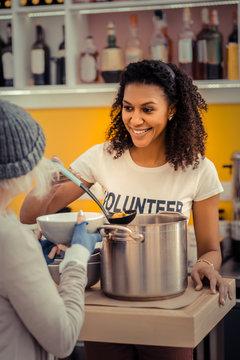 Joyful nice young woman giving the soup
