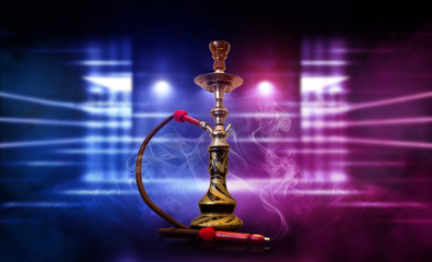 Smoking hookah on the background of an empty room. Multicolored neon light. Searchlight, laser blue and pink rays, smoke.