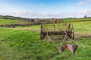 Old rusty horse drawn hay rake in a grass field with Devonshire countryside and hills in the background under a blue and cloudy sky on a bright day, with plenty of copy space included. Landscape.