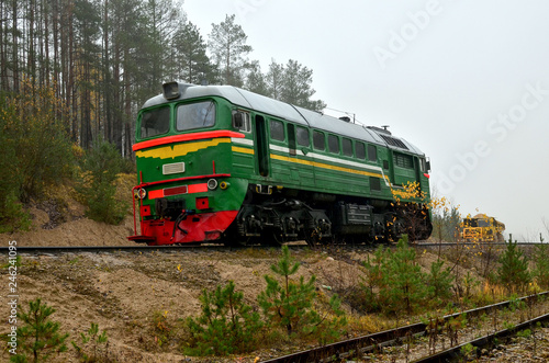 Freight train in a sand pit in cloudy foggy weather