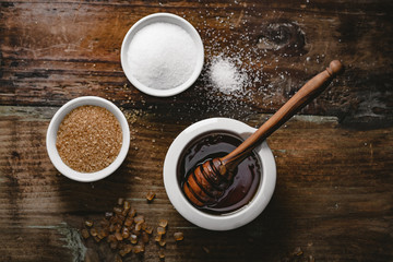 different kinds of sugar and maple syrup on a background