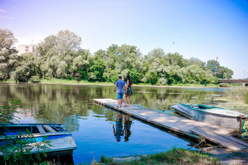 The girl and the guy hold hands on the shore of a romantic lake