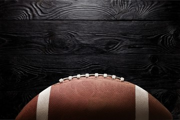 American football ball on black background illuminated by the
