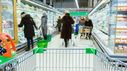 Timelapse - shopping trolley stands on the background of blurred customers in the aisle, people choose products Fotobehang