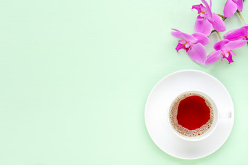 Light green wooden table with cup of tea and orchids.