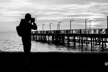 Young man taking a photo of the old pier.