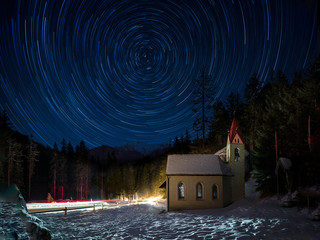 Beautiful wintery night in Southern Alps with church and star trails