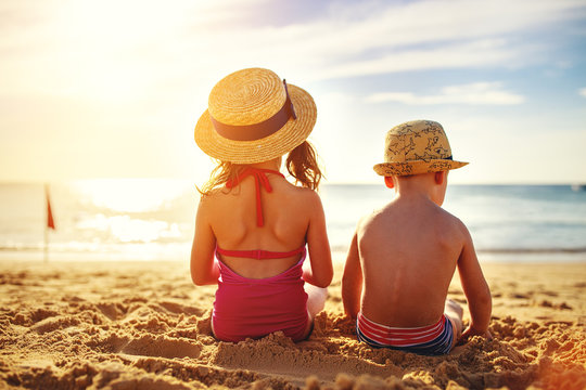 children boy and girl in swimsuit sit on beach back.