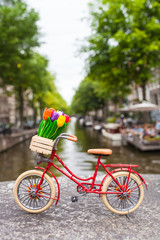 Colorful Amsterdam Spring City Bike Trip / Red dutch miniature bicycle with cute details at Amsterdam canal scenery background, tulip flowers in wooden crate, leather saddle, bright tires (copy space)