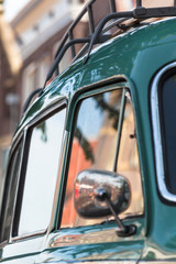 Road Trip to the Past / Detail of turquoise and chrome nostalgic car - side mirror, door, window, roof rack - at blurred mirroring town background