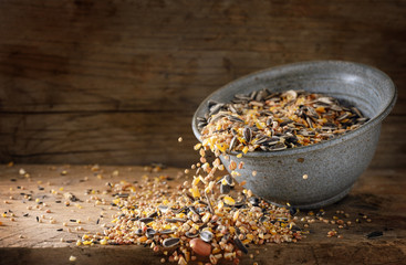 bird food for winter feeding, mixed seeds like sunflower, corn, millet and more are falling out of a bowl on a rustic wooden board, copy space, motion blur