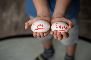 Eggs with the inscription Happy Easter in the hands of a child. Green background. Easter ideas. Space for text. Easter eggs. Living Coral lettering. Happy easter.
